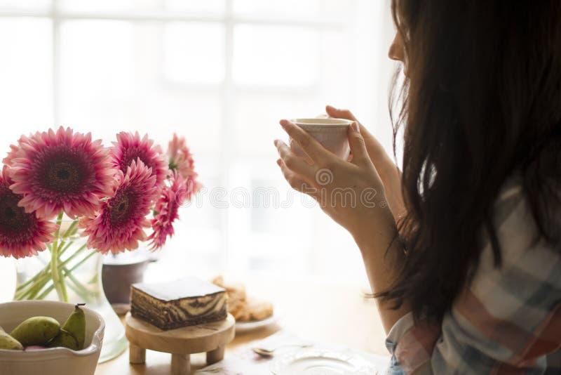 Een vrouw eet ontbijt bij het venster, op de lijst een boeket van bloemen en geurige koffie Goedemorgen thuis Vrije ruimte royalty-vrije stock foto's