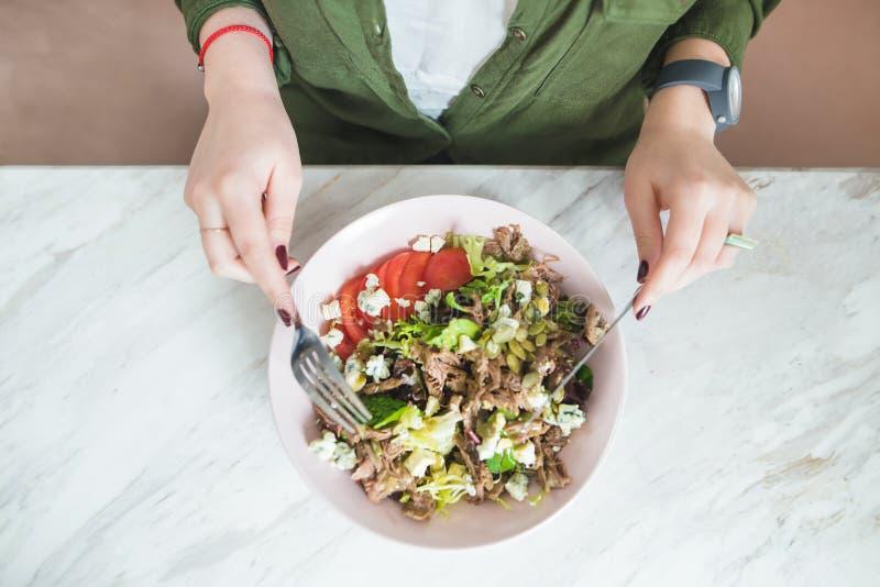 Een vrouw eet een rijke salade met een vork en een mes Hoogste mening stock foto