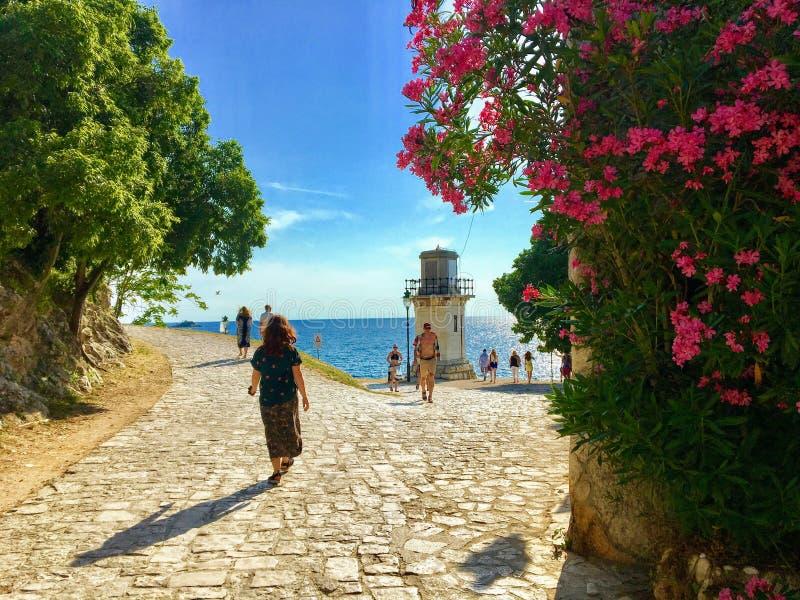 Een vrouw en andere toeristen en plaatselijke bewoners die rond een weg lopen die rond de oude stad van Rovinj, Kroatië gaat stock foto
