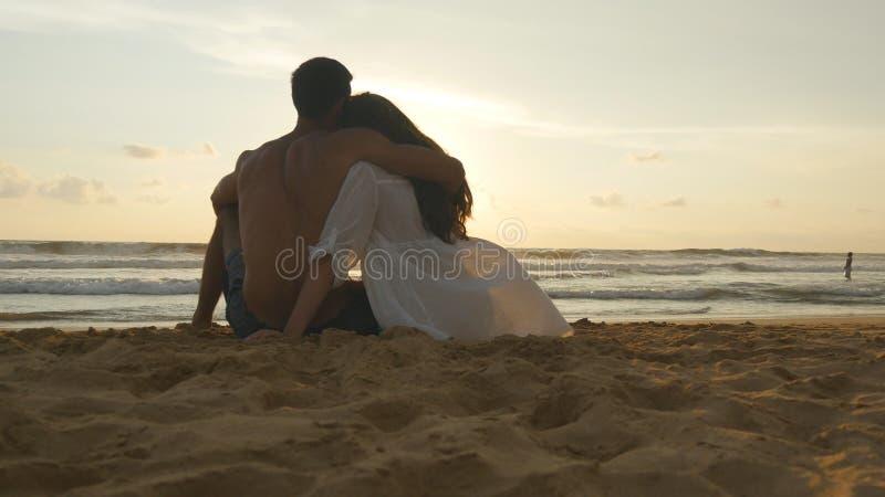 Een vrouw en een man zitten samen in het zand op de overzeese kust, bewonderend de oceaan en de landschappen Jong romantisch paar stock afbeelding