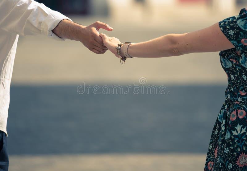 Een vrouw en een man houden handen tijdens een de zomergang rond de stad stock afbeeldingen