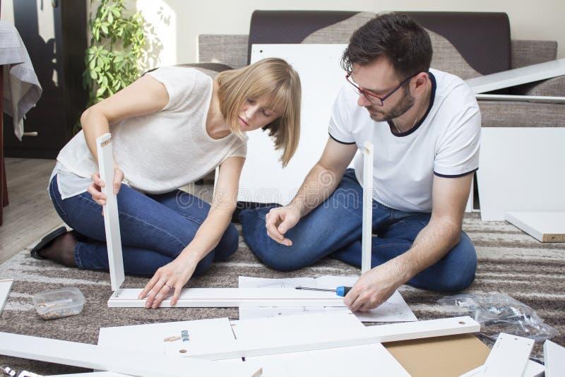 Een vrouw en een man in jeans en witte T-shirts zitten op het tapijt in de woonkamer van het vlakte en draai witte meubilair royalty-vrije stock afbeelding