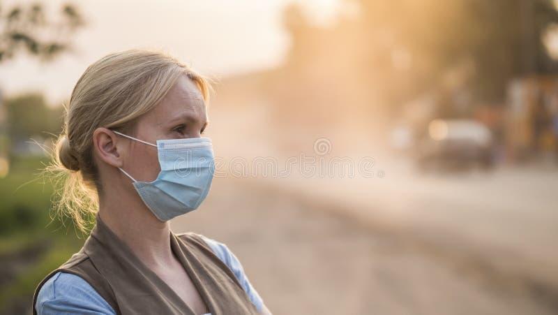 Een vrouw in een gaasverband is op een stoffige weg Het Concept van het milieu en van de Ecologie royalty-vrije stock afbeelding
