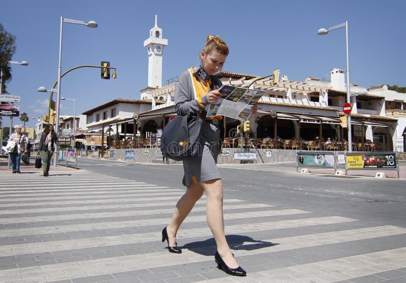 Een vrouw gaat bij een hotel in Arenal strand in Mallorca, Spanje werken stock fotografie