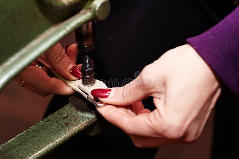 Een vrouw gebruikt een leerklinkhamer die een strook van leer vast te nagelen in de productie van handtassen/schoenen wordt gebru royalty-vrije stock foto
