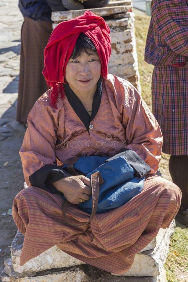 Een vrouw gekleed in traditionele Bhutanese wacht op de bus stock afbeelding