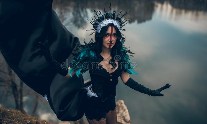 Een vrouw in het beeld van een fee en een tovenares die zich over een meer in een zwarte bevinden kleden zich en een kroon stock afbeelding
