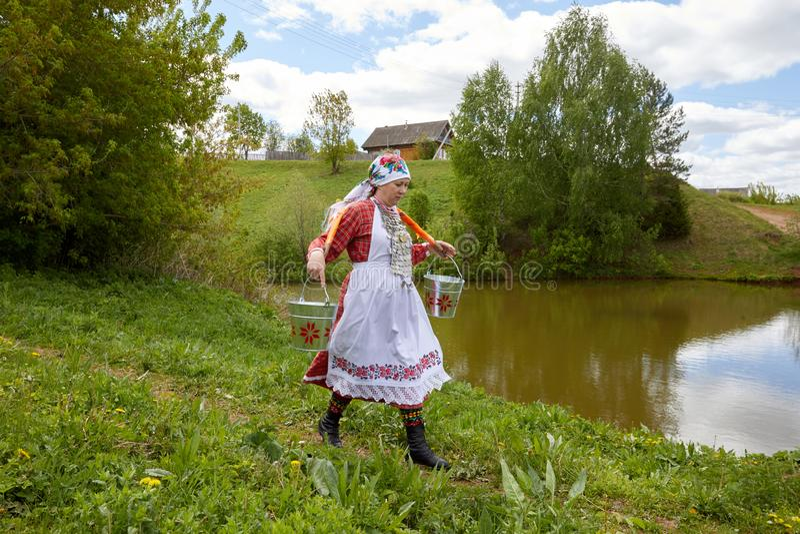 Een vrouw in het dorp is bezig geweest met huishouden Het meisje draagt emmers water uit een schone bron royalty-vrije stock foto