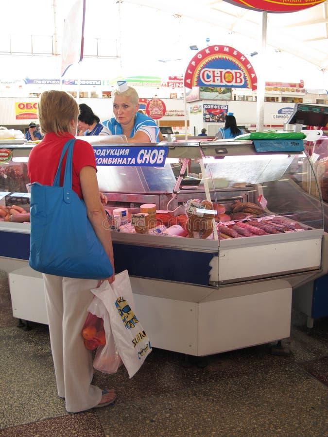Een vrouw het kopen vlees voor verkoop in de Komarovsky-markt, Minsk Wit-Rusland stock foto's