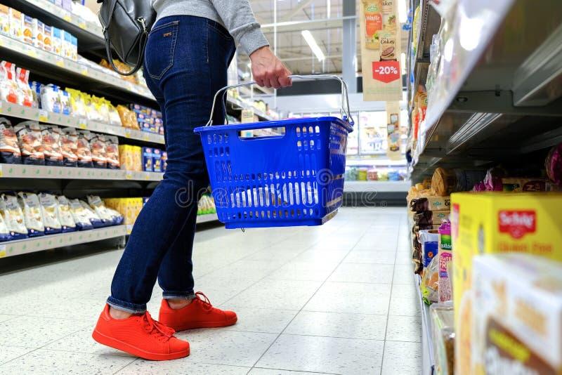 Een vrouw houdt het handvat van de kruidenierswinkelkar, die onderaan de doorgang in de supermarkt gaan Koop het product Heilige- royalty-vrije stock afbeeldingen
