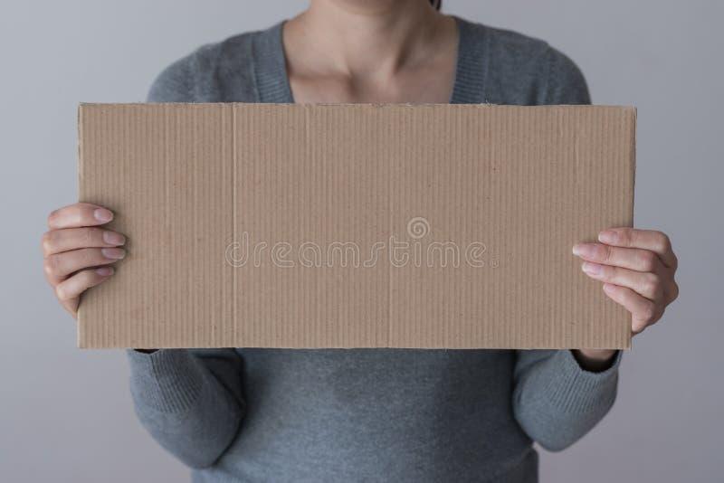 Een vrouw houdt leeg teken vooraan haar gezicht stock foto
