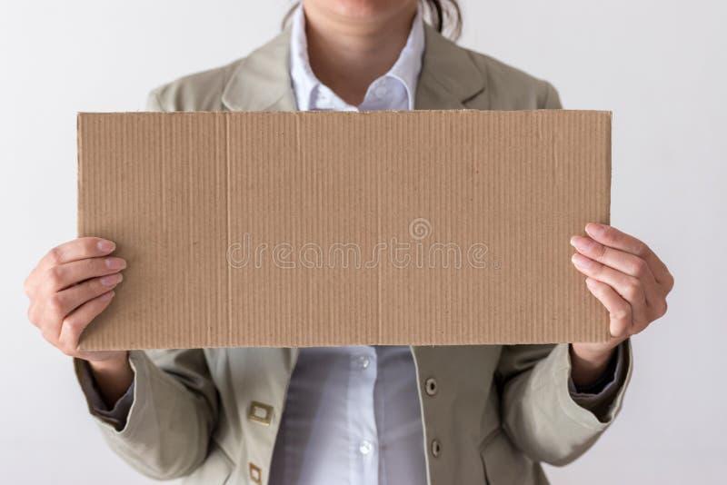 Een vrouw houdt leeg teken vooraan haar gezicht royalty-vrije stock afbeelding
