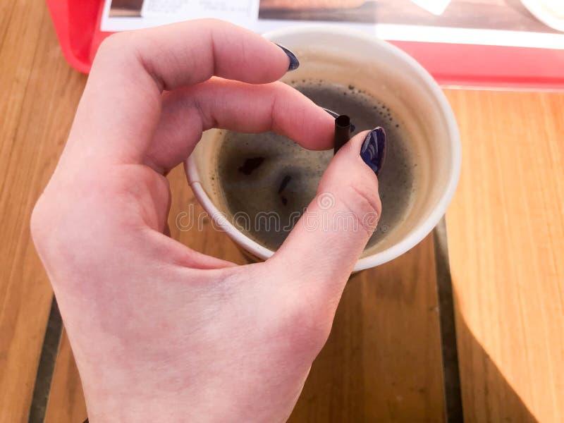 Een vrouw houdt met een mooie manicure op haar vingers een buis in een kop van snel zwarte hete sterke natuurlijke koffie van sne royalty-vrije stock afbeeldingen