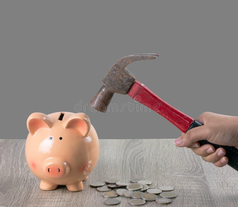 Een vrouw houdt een roestige hamer om een spaarvarken te breken stock foto