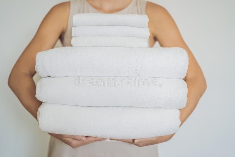 Een vrouw houdt een stapel witte handdoeken Concept de dienst i royalty-vrije stock foto