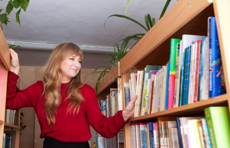 Een vrouw kiest een boek in een bibliotheek royalty-vrije stock afbeeldingen