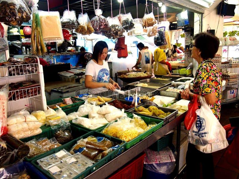 Een vrouw kiest van een grote verscheidenheid van vers voedsel van een markt in de stad van Tampines in Singapore stock afbeelding
