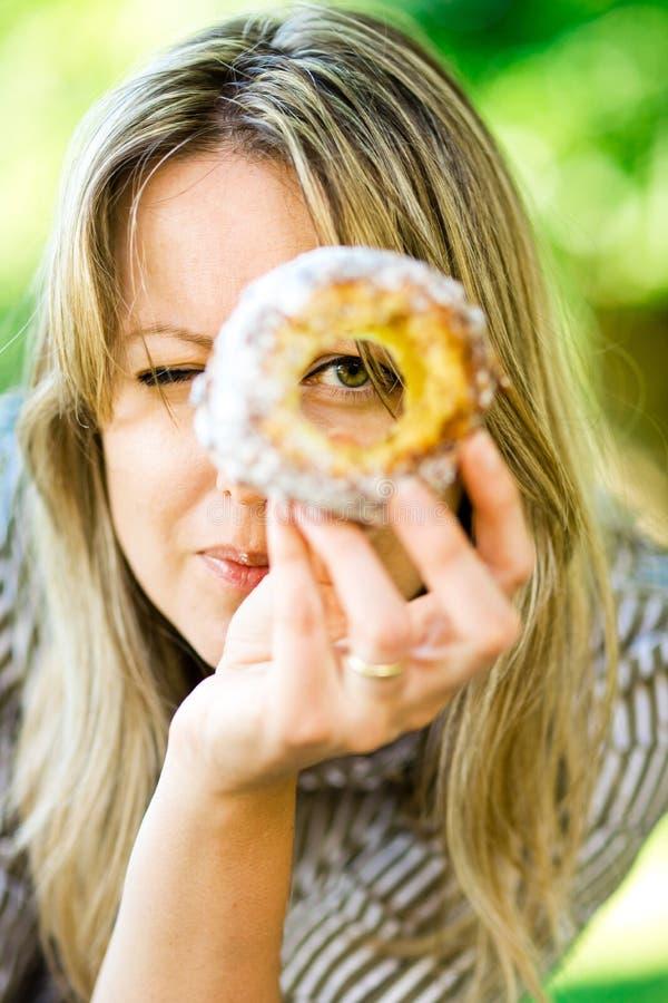 Een vrouw kijkt door het gat in cake Trdelnik stock foto