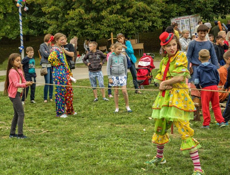 Een vrouw kleedde zich in de spelen van een clownkostuum met kinderen in Fr royalty-vrije stock afbeeldingen