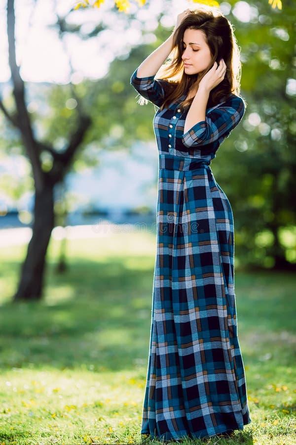 Een vrouw in lange geruite kleding Romantisch meisje in het de lentepark Een vrouw loopt in het park in een toevallige kleding Gr royalty-vrije stock foto's