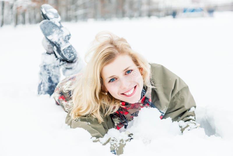 Een vrouw ligt bij de sneeuw in het park stock afbeelding