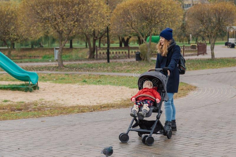 Een vrouw loopt in het park met een wandelwagen en een klein kind stock fotografie