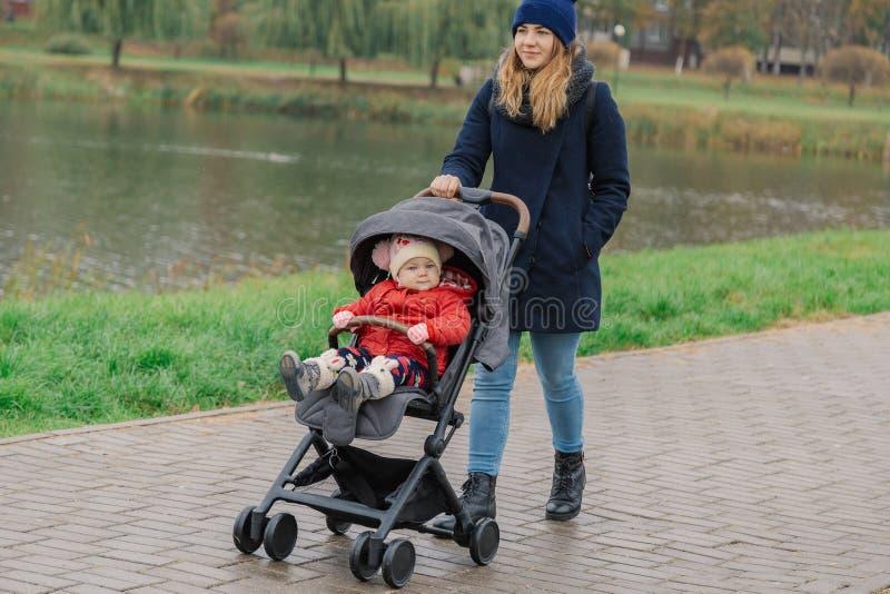 Een vrouw loopt in het park met een wandelwagen en een klein kind dichtbij het meer stock fotografie