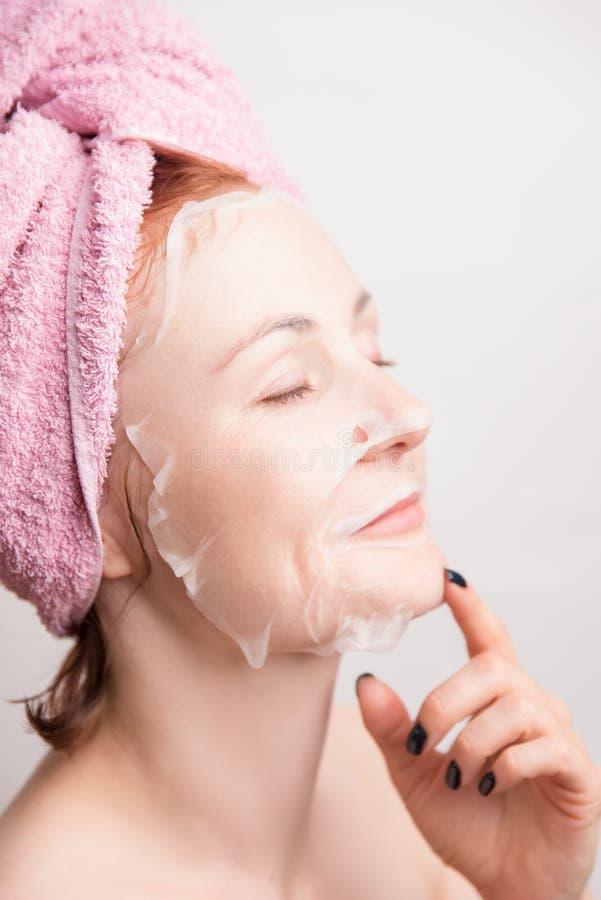 Een vrouw maakt een kosmetisch masker voor het bevochtigen van de huid royalty-vrije stock foto's