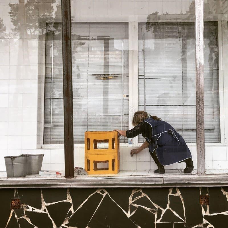 Een vrouw maakt een lege opslagvoorzijde op de straten van Tbilisi - GEORGIË schoon - Hoofdstadschoonheid royalty-vrije stock afbeeldingen