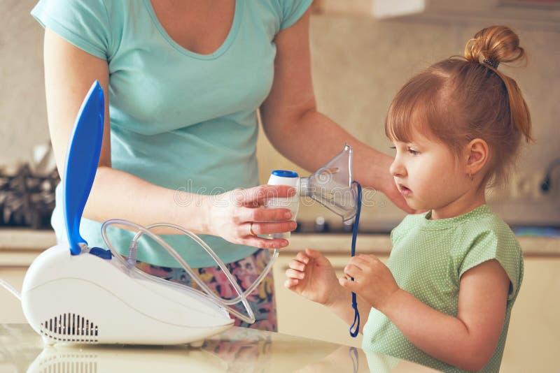 Een vrouw maakt tot inhalatie thuis aan een kind brengt het verstuiversmasker aan zijn gezicht inhaleert de damp van het medicijn royalty-vrije stock foto