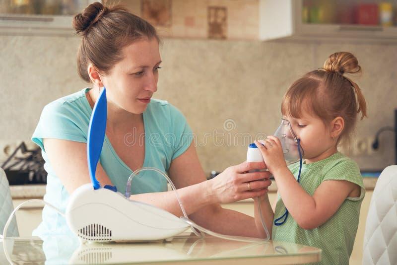 Een vrouw maakt tot inhalatie thuis aan een kind brengt het verstuiversmasker aan zijn gezicht inhaleert de damp van het medicijn stock foto's