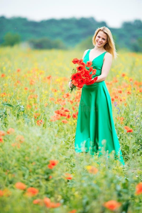Een vrouw met charmante glimlach tijdens lichte regen met een boeket van stock foto's
