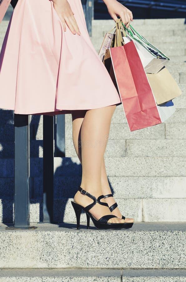 Een vrouw met document zakken rust na het winkelen stock afbeelding