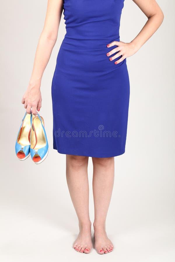 Een vrouw met een blauwe kleding die hoge hielen houden stock foto's
