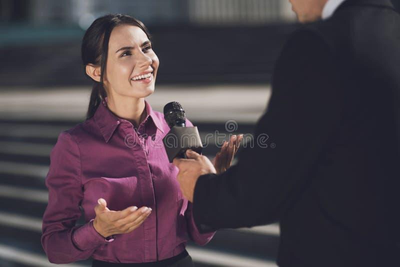 Een vrouw met een glimlach op haar gezicht beantwoordt de vraag Een mens houdt een microfoon luisterend aan een antwoord royalty-vrije stock afbeelding
