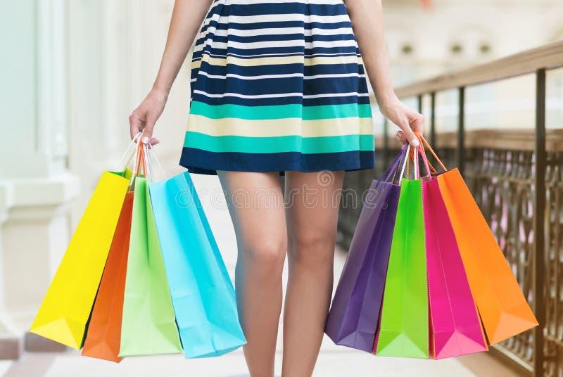 Een vrouw met heel wat kleurrijke het winkelen zakken stock foto's