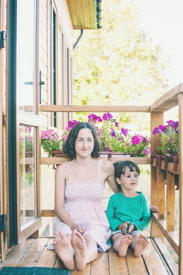 Een vrouw met een kind zit op de veranda royalty-vrije stock fotografie