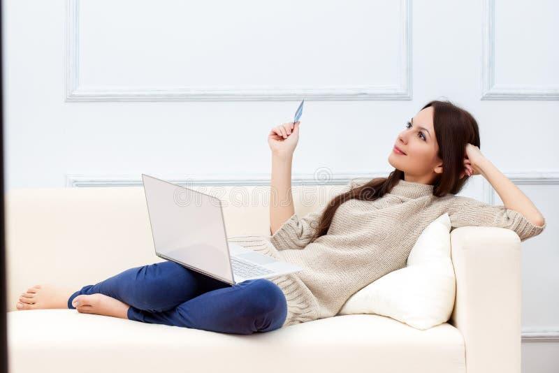 Een vrouw met laptop is op de bank stock fotografie