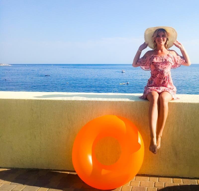 Een vrouw met een mooi cijfer zit op een concrete omheining voor het overzees Opblaasbare Nogshinahschinysinaasappel stock foto