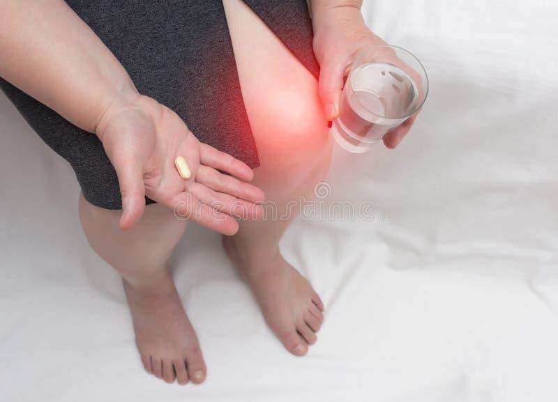 Een vrouw met een pijnlijke knie houdt een chondroprotectortablet en een glas water, glucosamine en chondroitin sulfaat in haar h royalty-vrije stock afbeeldingen