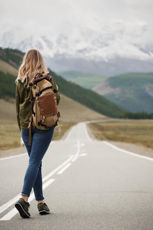 Een vrouw met een rugzak en weg het uitrekken zich in de afstand stock fotografie
