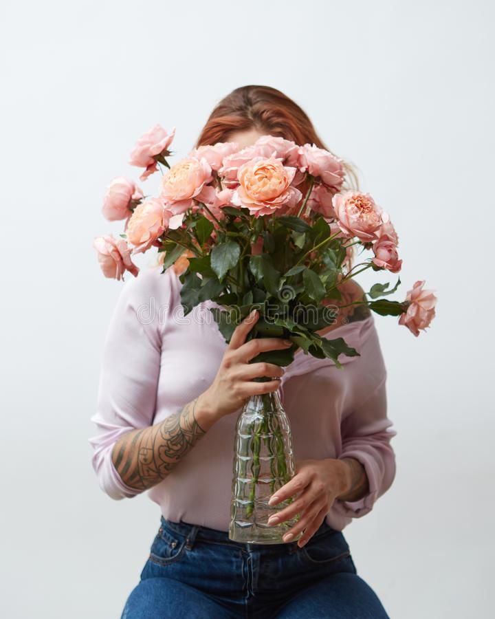 Een vrouw met een tatoegering die een groot boeket van roze rozen in een glasvaas houden rond een grijze achtergrond met exemplaa stock afbeeldingen