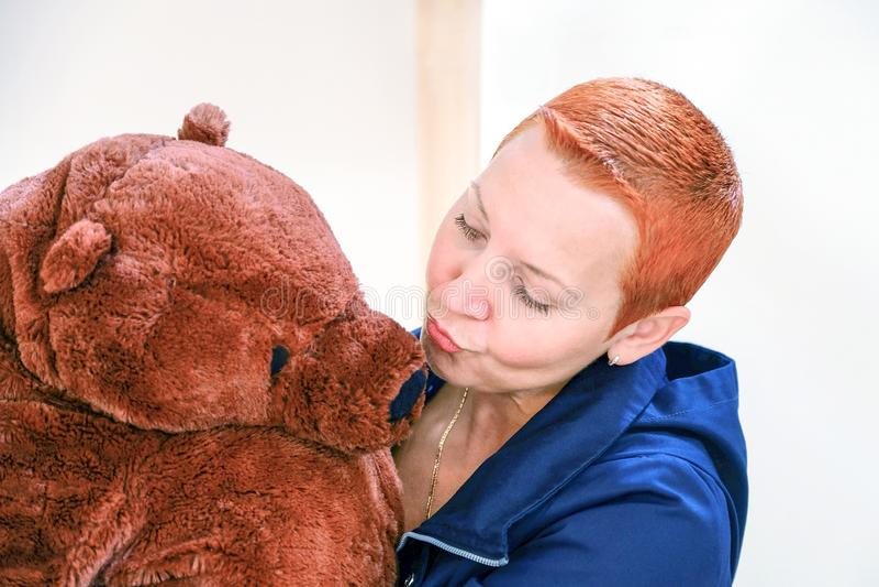 Een vrouw met een Teddybeer Vrouwen kussende die Teddybeer op lichte achtergrond wordt geïsoleerd stock afbeelding