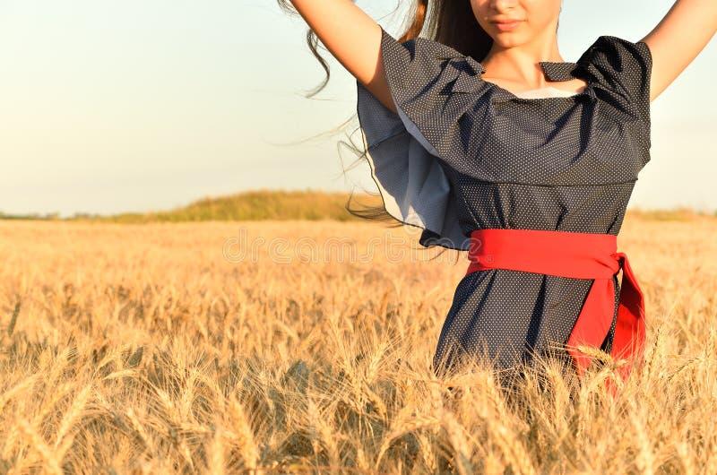 Een vrouw met unraised haar en een pindakleding is onder wheat& x27; s tarwe stock foto's