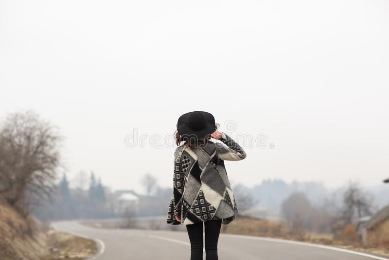 Een vrouw in een mooie grijze cardigan en zwarte hoedenritten langs de manier Achter mening stock foto's