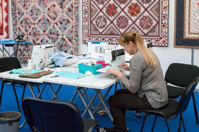 Een vrouw naait een dekbed op een naaimachine, op de achtergrond van lapwerk stock afbeelding