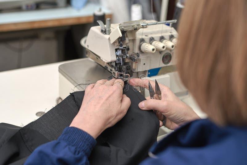 Een vrouw naait op een elektrische naaimachine stock foto