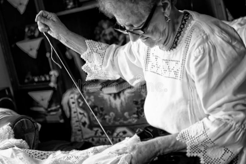 Een vrouw naait traditionele tafelkleden stock afbeelding