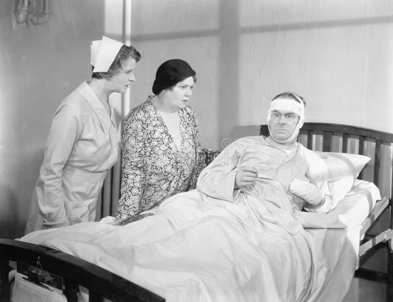 Een vrouw naast haar echtgenoot in een het ziekenhuisbed met verpleegster het aanwezig zijn (Alle afgeschilderde personen leven n stock fotografie