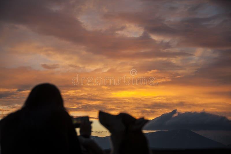 Een vrouw neemt een foto van een zonsondergang met haar smartphone royalty-vrije stock fotografie